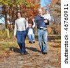 Happy family walking on path during autumn - stock photo