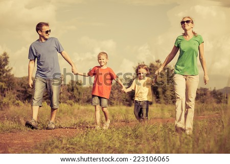 Happy family walking on the road at the day time. Concept of friendly family. - stock photo