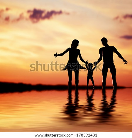 Happy family walking together hand in hand at sunset. Mother, father and a little child