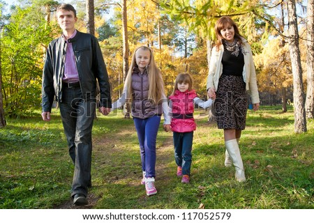 Happy family walking together in autumnal park - stock photo
