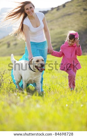 Happy family walking with dog in green field - stock photo