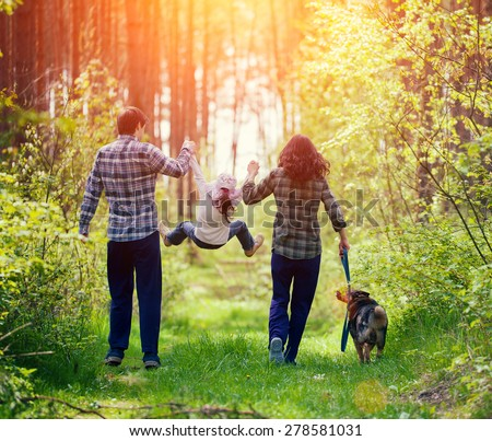 Happy family walking with dog in the forest - stock photo
