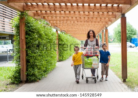 Happy family walking with shopping cart going to a supermarket.
