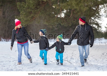 Happy family walks and playing with snow in winter forest - stock photo