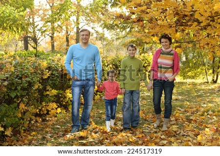 Happy family walks in the autumn park