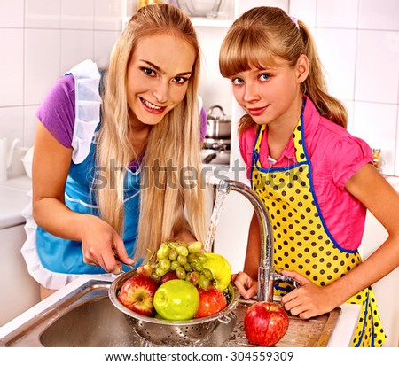 Happy  family washing fruit at kitchen. Woman cooking at home - stock photo