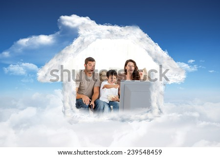 Happy family watching a movie on television together on the sofa against bright blue sky with clouds - stock photo