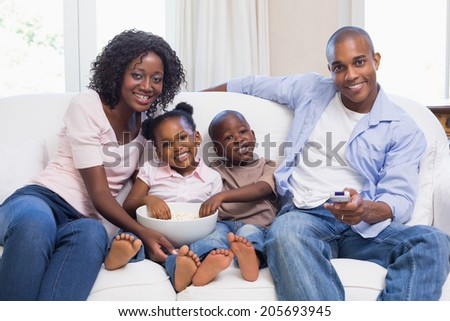Happy family watching television together at home in the living room - stock photo