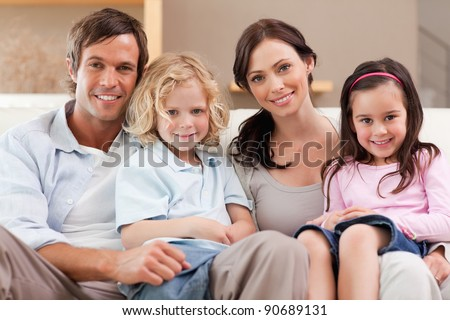 Happy family watching television together in a living room - stock photo