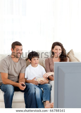 Happy family watching television while eating popcorn together on the sofa