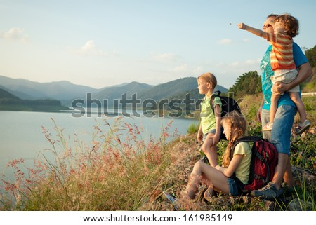 Happy family watching the sunset on the lake