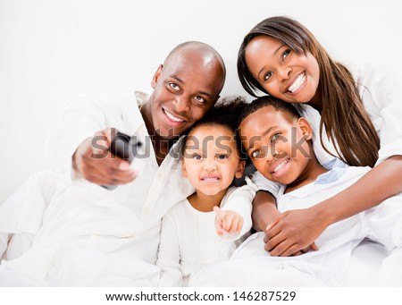 Happy family watching tv in bed - isolated over white - stock photo