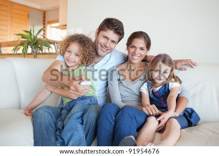 Happy family watching TV together in their living room - stock photo
