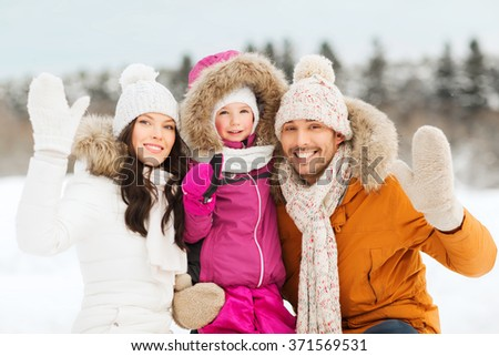 happy family waving hands outdoors in winter - stock photo