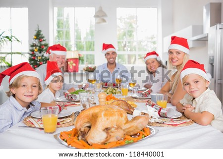 Happy family wearing santa hats around the dinner table at christmas - stock photo