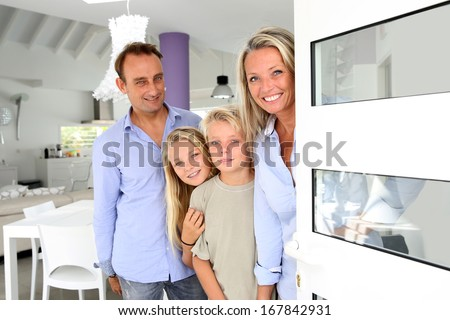 Happy family welcoming people at home - stock photo