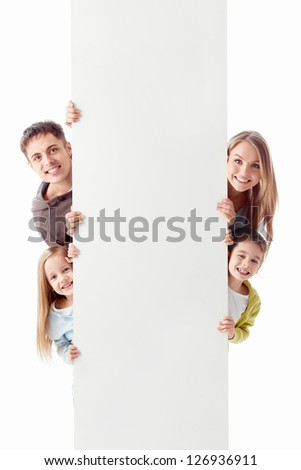 Happy family with a billboard on a white background - stock photo