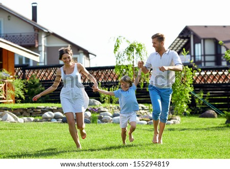 Happy family with a child by the house - stock photo