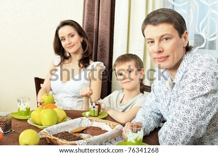 Happy family with a child having a dinner at home.