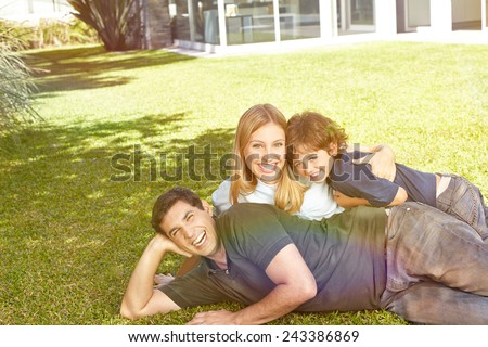 Happy family with a child laying in the garden in front of a house - stock photo
