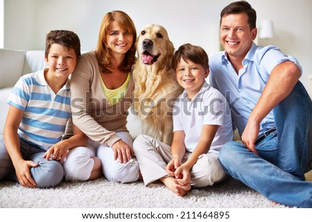Happy family with a dog in their flat - stock photo