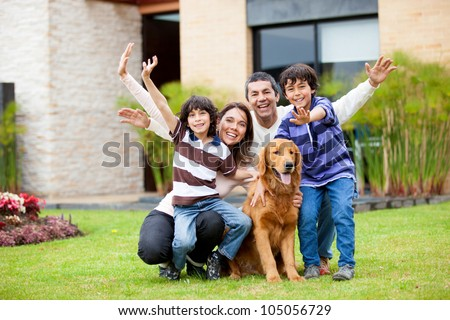 Happy family with a dog outside their house - stock photo