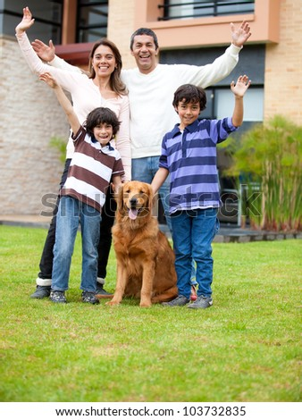 Happy family with a dog outside theit house - stock photo