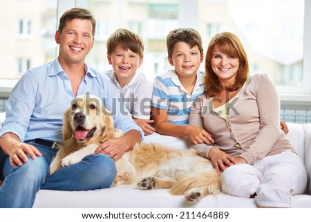 Happy family with a dog sitting in the room - stock photo