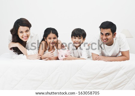 Happy family with a piggy bank on the bed - stock photo