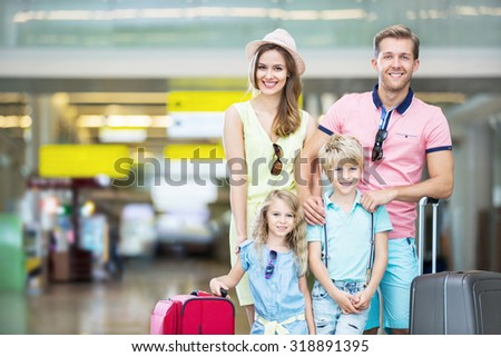 Happy family with a suitcase at the airport