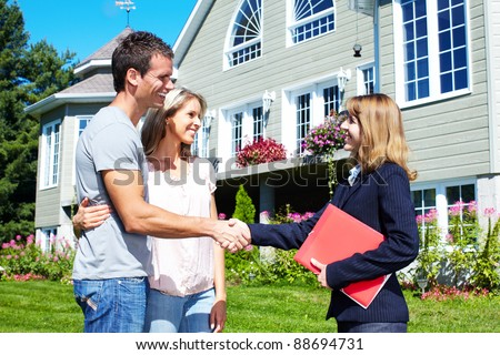 Happy family with agent realtor near new house. - stock photo