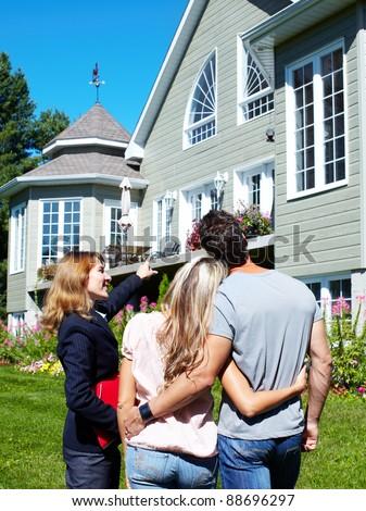 Happy family with agent realtor near new house. - stock photo