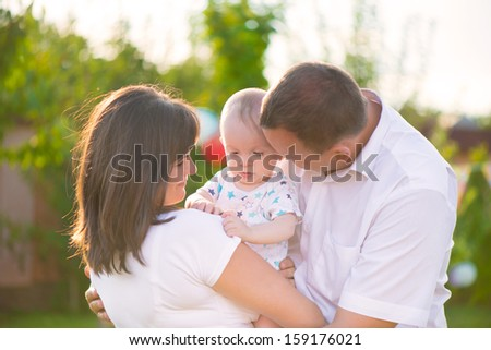 Happy family with baby son in park at sunny day