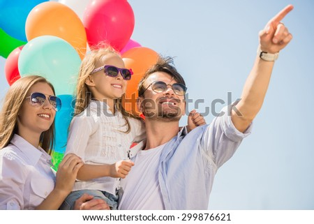 Happy family with balloons looking up outdoor on a summer day. - stock photo