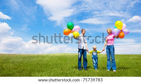 happy family with balloons outdoor on a summer day - stock photo