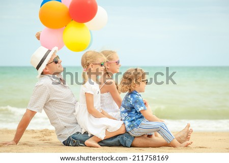 Happy family with balloons sitting on the beach at the day time. Concept of friendly family. - stock photo