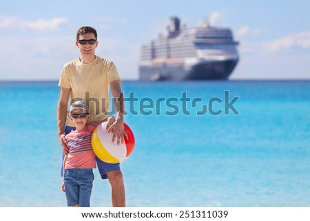 happy family with beach toy enjoying summer vacation with cruise ship in the background - stock photo