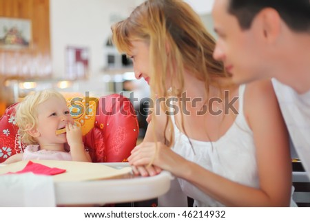 Happy family with blond little girl eating bread - stock photo