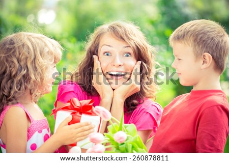 Happy family with bouquet of flowers and gifts outdoors. Young beautiful mother with son and daughter lying on green grass. Spring holiday concept. Mother's day. Surprise and joy