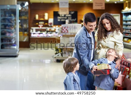 Happy family with boxes of gifts in shop in the foreground - stock photo