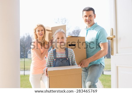 Happy family with cardboard boxes entering new home - stock photo