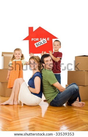 Happy family with cardboard boxes in their new home showing the house sold sign - isolated