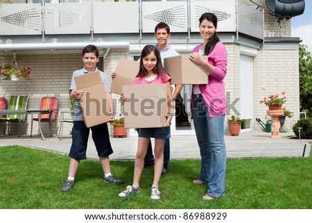 Happy family with cardboard boxes moving in their new home - stock photo
