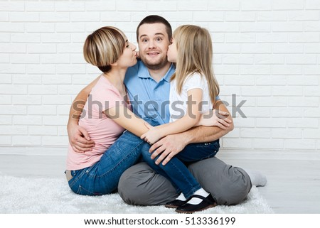 Happy family with child at home. Mother and daughter kissing daddy