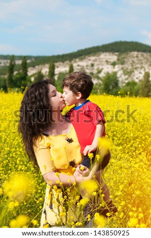 Happy family with child -beautiful mother hug with her son,resting in blossom spring garden with field flowers on nature looking happy smiling outdoors.Smiling girl with healthy hair on nature