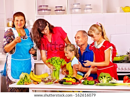 Happy family with child cooking at kitchen. Grandfather and grandmother. - stock photo