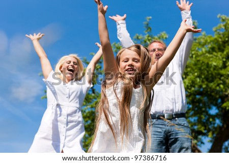 Happy family with child jumping in a meadow in summer - stock photo