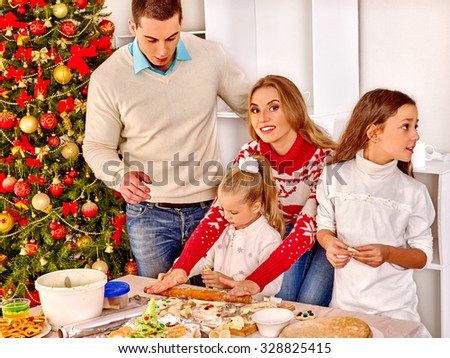 Happy family with children and parents rolling dough near Christmas tree.