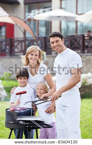 Happy family with children at barbecue - stock photo