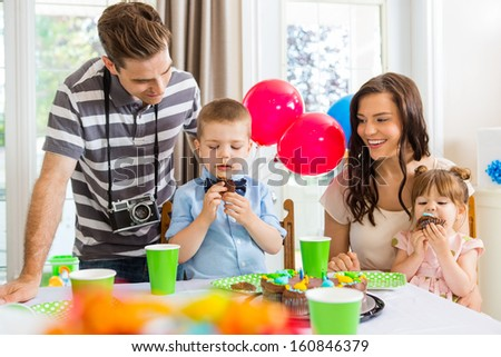 Happy family with children eating birthday cake at home
